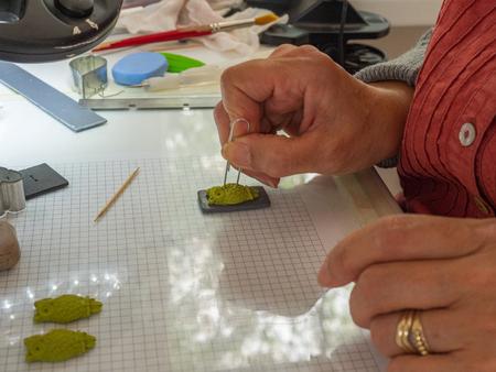 Frauenhand, die Eulenknopf vom Polymerton macht. Hobby, Handwerk Hintergrund Standard-Bild - 81278510