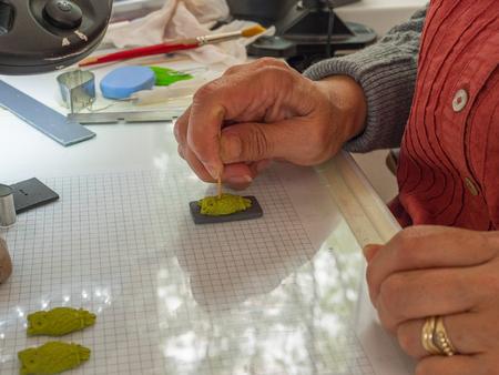 Frauenhand, die Eulenknopf vom Polymerton macht. Hobby, Handwerk Hintergrund Standard-Bild - 81279047