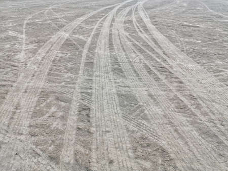 Abstract texture of wheel marks on soil roads. Tire marks of car