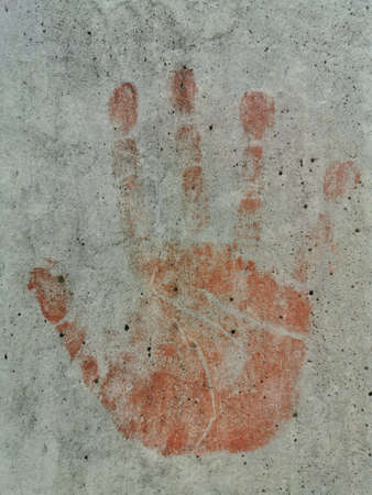 Red hand marks on concrete walls. Symbol stop.