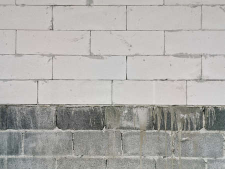 Lightweight concrete or aerated bricks and concrete blocks used together in the construction.