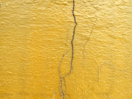 Golden cracked concrete wall surface.
