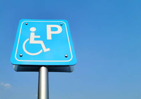 Parking signs for disabled wheelchairs, background blue sky.