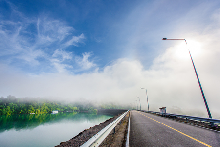 An asphalt road view at Ratchaprapa Choew Lan Dam in Surat Thani, Thailand. A view of beautiful fog, bright, clear blue sky at dam road. Banco de Imagens