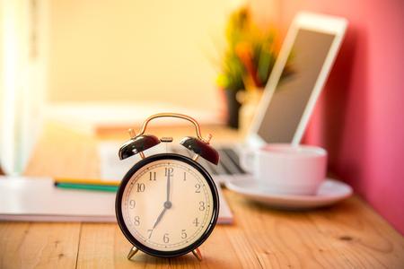 テーブルの背景にぼかしノートパソコンとお茶のカップで7時にアラーム。おはようございます、新しい仕事の日の始まり。ビジネスコンセプト。