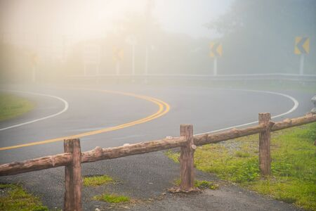 An asphalt mountain highway view with sharp curve in Nan, Thailand. A view of fog and sharp curve road with no over taking sign.