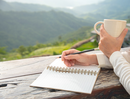 A closeup of young woman holding a cup of coffee and taking a note with beautiful mountain view. A warm morning coffee and note book in woman hands with copy space. Banque d'images