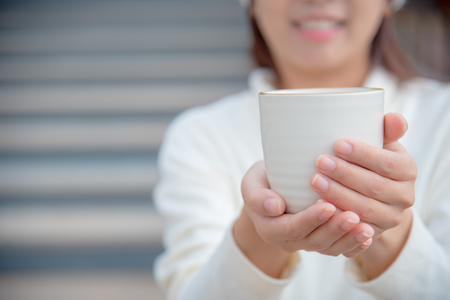 comfortable: An asian young happy woman with tea cup in her hands and blurred background. An image of hot beverage in woman hands with copy space.