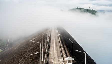 An asphalt road high view at Ratchaprapa Choew Lan Dam in Surat Thani, Thailand. Beautiful fog at dam road.