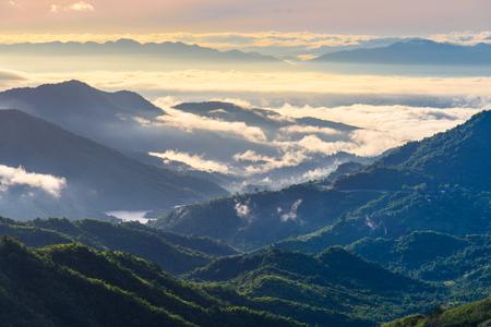 Romantische zee van mist over vallei met bergachtergrond bij wazige zonsopgang. Nevelig altijdgroen berglandschap.