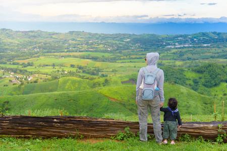 De gelukkige handen van de moederholdingsdochter ontspannen met blauw hemel en berglandschap. Avonturenreizen van ouder en kind. Stockfoto