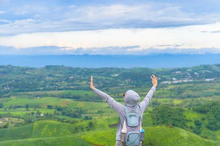De gelukkige vrouw ontspant met wapens omhoog en berglandschap op blauwe hemeldag. Vrijheid en stressvrij moment. Stockfoto