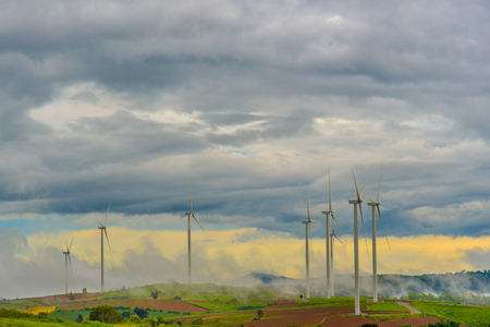 Wind generators turbines and smoky sky. Beautiful mountain landscape with wind generators turbines at Khao Kho mountain, Thailand. Renewable energy concept. Stock Photo