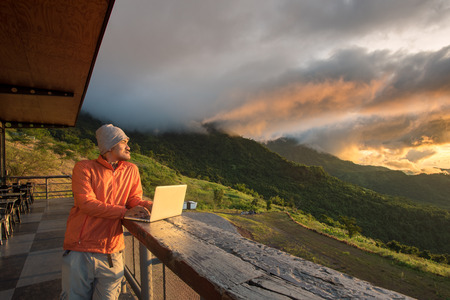 Aziatische knappe hipster freelance baard man permanent, ontspannen en werken via 5 gwireless bij berg café tijdens zonsopgang.
