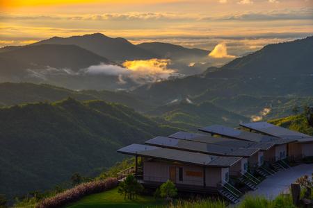 Dramatische levendige zonsopgang met romantische bewolkte hemel en bergachtergrond. Schoonheid van de dageraad zonnestraal scène bij resort.