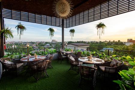 Dekrestaurant met stadsmening in ochtendzonlicht. Buffetontbijt in restaurant in Aziatische stijl.