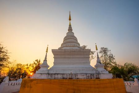 Wat Phra That Khao Noi in Nan, het noorden van Thailand bij zonsopganghemel. De heilige stupa met relikwieën van Boeddha omsloten met pagodedeken. Stockfoto