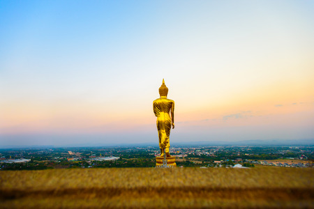 The sacred standing statue of Buddha at Wat Phra That Khao Noi in Nan, north of Thailand with vivid sunrise sky background.