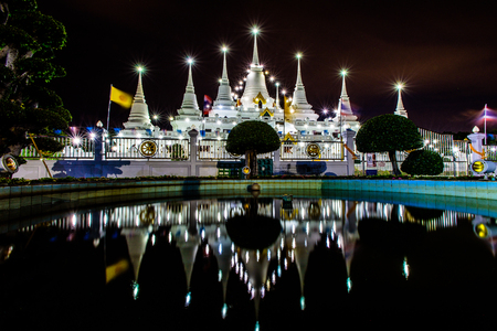 Architecture of Phra Thu Tang Ka Jay Dee at Wat Asokaram in Samut Prakarn, Thailand. Glittering pagoda containing Buddha's relics and reflection over pond at night.