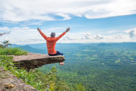 Happy man sitting and relaxing, arms up, with mountain landscape on blue sky day. Freedom and stress free moment. Stock Photo