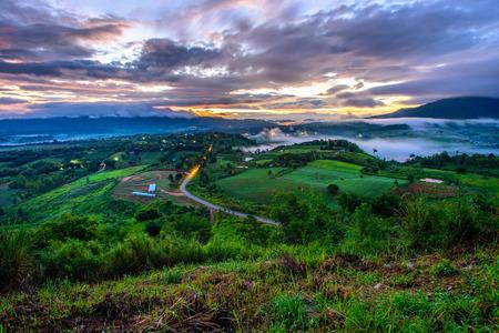 Dramatische levendige zonsopgang, zee van mist met romantische bewolkte hemel, bergachtergrond. Schoonheid van de valleinscène van de dageraadzonnestraal bij Ngo van Khao Takhian, Petchabun, Thailand. Stockfoto