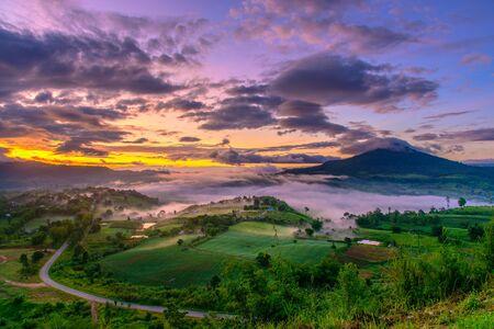 Dramatische levendige zonsopgang en mist met romantische bewolkte hemel en bergachtergrond. Schoonheid van de scènescène van de dageraadzonnestraal bij Ngo van Khao Takhian, Petchabun, Thailand.