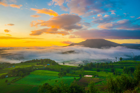 Dramatic vivid sunrise, sea of fog with romantic cloudy sky, mountain background. Beauty of dawn sunbeam valley scene at Khao Takhian Ngo, Petchabun, Thailand.