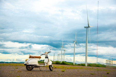 Parking scooter and beautiful cloudy mountain landscape with wind generators turbines at sunset, Khao Kho mountain, Thailand. Renewable energy concept.