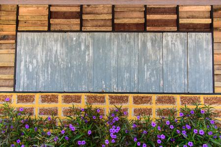 Oud houten plank en bakstenen muurpatroon. Antieke ruwe en rustieke muur van landelijk huis met bloemen.