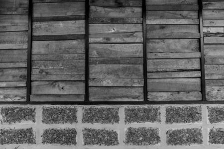 Old wooden plank and brick pattern. Antique rough and rustic fence of rural house in black and white Stock Photo