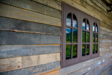 Old wooden plank wall and window pattern. Antique rough and rustic wall of rural house. Stock Photo