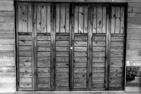 Gesloten houten vouwdeuren bij bungalow in platteland. Vouwend deurenpatroon in zwart-witte toon.