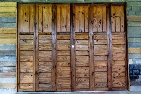 Gesloten houten vouwdeuren bij bungalow in platteland. Vouwend deurenpatroon. Stockfoto