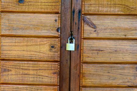 Close-up van het oude deurslot. Ingang afgesloten voor beveiliging. Oude houten deur op slot.
