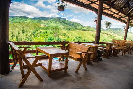 Dekrestaurant met mooie bergmening in zonlicht. Houten decoratierestaurant en de achtergrond van het bergvalleiland.