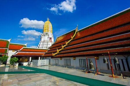 Wat Phra Sri Mahathat in Pitsanulok, north of Thailand, on bright blue sky. Temple court, marble floor with large temple bell, statue of Buddha and stupa view.
