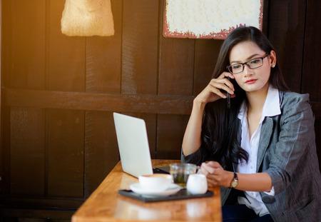 Jonge vrouwelijke freelancer die online bij laptop werken en die op marketing kwesties op cel bespreken. Bedrijfsconcept.