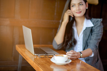 Blur of young female freelancer working online at laptop and discussing on marketing issues on cell. Business concept. Stock Photo
