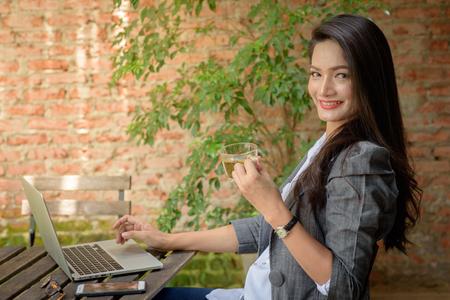 Gelukkige toevallige mooie onderneemster het drinken thee op het werk. Freelance levensstijl bij coffeeshop. Stockfoto