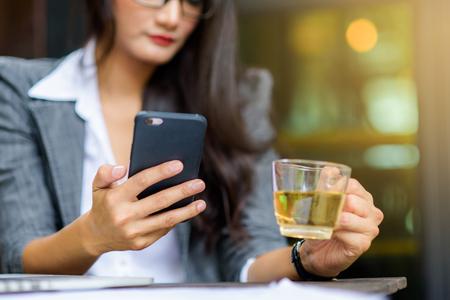 Jonge vrouwelijke freelancer die e-mail controleert op cel tijdens theepauze. Bedrijfsconcept.