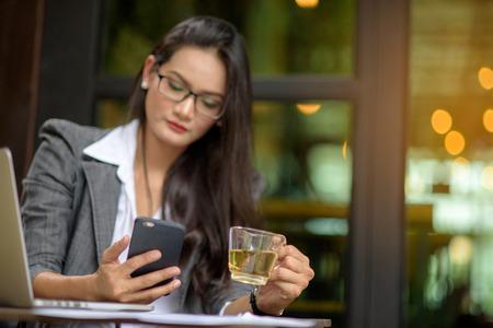 Jonge vrouwelijke freelancer die e-mail controleert op cel tijdens theepauze met bokehachtergrond. Bedrijfsconcept.