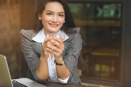 Happy casual beautiful businesswoman drinking tea at workplace. Freelance lifestyle at coffee shop. Stock Photo