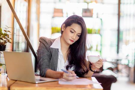 Jong wijfje die freelancer aan marketing plan werken bij koffiewinkel. Bedrijfsconcept.