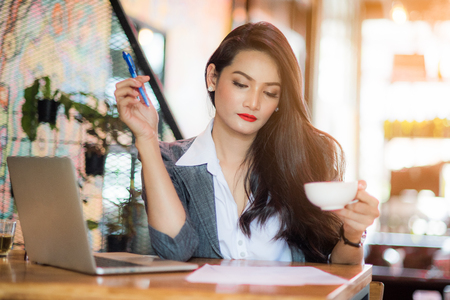 Young female freelancer working on marketing plan at coffee shop. Business concept. Stock Photo