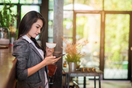 Jonge vrouwelijke freelancer die e-mail controleert op cel tijdens koffiepauze. Bedrijfsconcept.