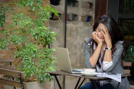 Vermoeide onderneemster die een hoofdpijn wegens faillissement heeft. Slaperige werknemer overwerkt het maken van fout. Bedrijfsconcept. Stockfoto