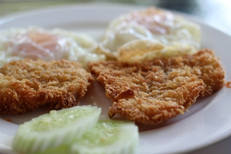 Fried fish served with eggs and cucumber