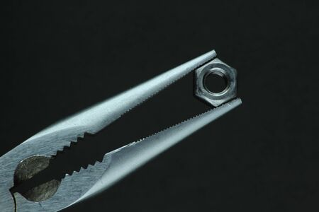 Long nose plier and nut on black background Stock Photo - 18846865