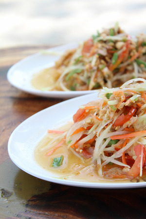 somtum: Somtum Thai food and spicy food on a white dish. Stock Photo
