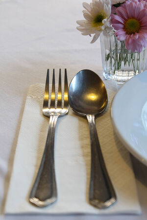 clothe: Fork, spoon and white dish on white clothe table